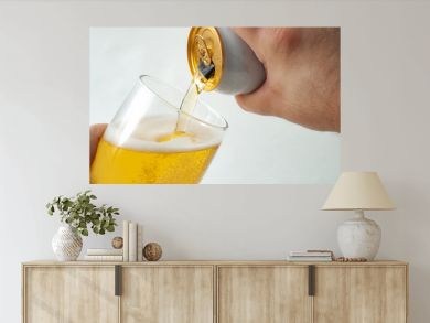 Alcoholic beverage, drinking alcohol and alcoholic content concept with close up on a hand pouring from a can of beer into a clear glass isolated on white background