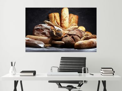 Assortment of baked bread and bread rolls on rustic black bakery table background
