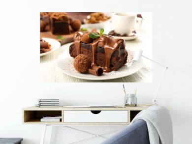 A piece of chocolate cake with mint on the table, close-up
