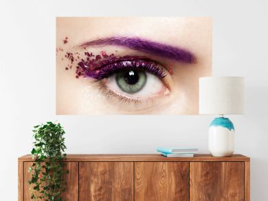 Close-up of a woman's open eye with a shiny trendy makeup in violet tones with sparkles