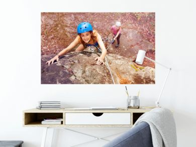 Climber in helmet reaching top of the mountains
