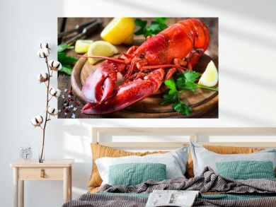 Steamed red lobster on a wooden cutting board with parsley and lemon