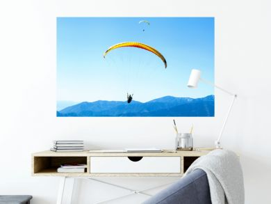 Two Paragliders soaring in the sky over the blue mountains