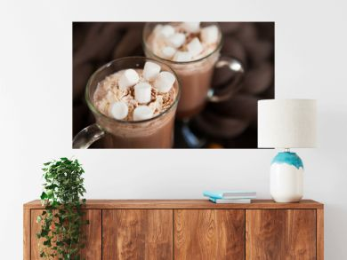 Two glasses with Hot chocolate garnished with whipped cream, marsmallow and cocoa powder on  wooden background with Cozy plaid from merinose wool