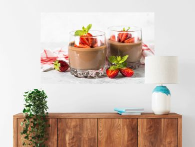 Chocolate dessert of whipped cream and strawberries in glass.