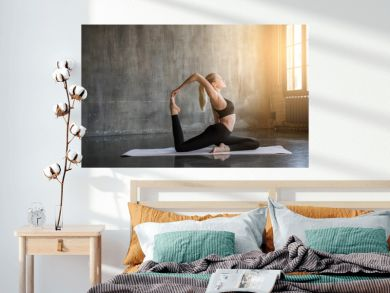 Young woman doing ashtanga yoga practice in a loft studio, surrounded by bright sunlight. Beutiful girl meditating makes herself a healthy body and strengthening the spirit.