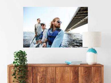 Pensive dreamy men of different ages sailing yacht together and enjoying floating on river, they looking around