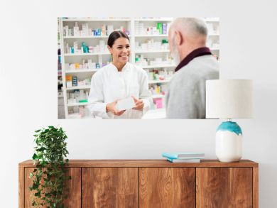 Medicine, pharmaceutics, health care and people concept - Happy female pharmacist giving medications to senior male customer