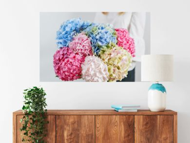 hydrangea , beautiful spring bouquet. Young girl holding a flowers arrangement with various of colors. white wall.