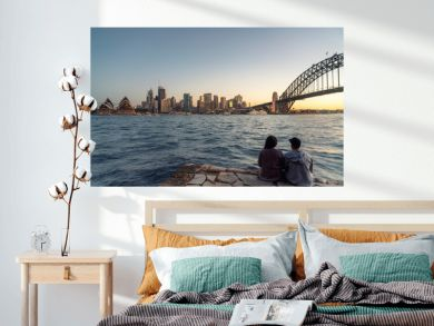 Romantic couple looks at Sydney skyline at dusk in Sydney New South Wales, Australia.