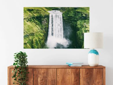 Iceland waterfall Skogafoss banner nature landscape. Panoramic destination in Icelandic famous world landmark tourist attraction on South Iceland. Aerial drone view of top waterfall.