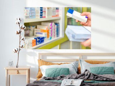 Pharmacist holding medicine box in pharmacy drugstore.