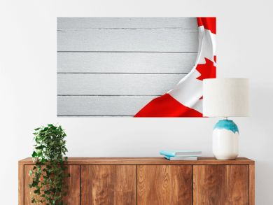Canadian flag, on top of white wood. Wrinkled fabric.