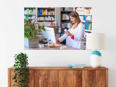 Female pharmacist working in chemist shop or pharmacy. Pharmacist using the computer at the pharmacy. Portrait of young female pharmacist holding medication while using computer at pharmacy counter