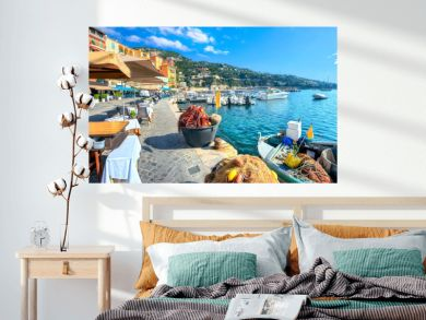 Street scene with cafe and fishing boat in resort town Villefranche-sur-Mer. Cote d'Azur, France