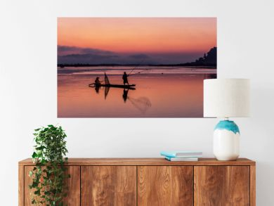 Silhouette of fisherman on wooden boat in nature lake with sunrise