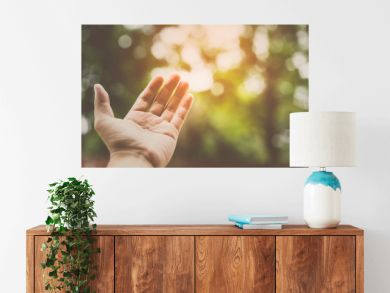 Bare hand with shining light and tree background