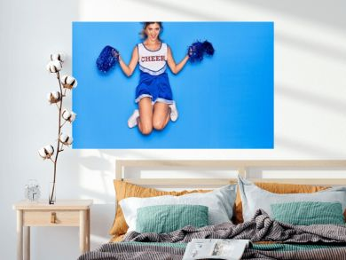 Young beautiful girl wearing cheerleader uniform smiling happy. Jumping with smile on face using pompoms over isolated blue background