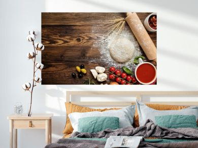 Pizza dough with ingredients on wood