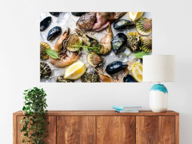 Fresh seafood with herbs and lemon on ice. Prawns, fish, mussels, scallops over steel metal tray