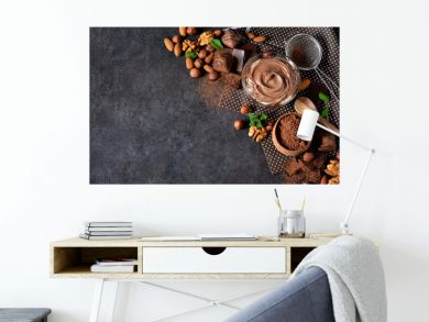 Black food background with cocoa, nuts and chocolate paste.