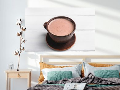 Hot cocoa with milk in brown clay cup, on table of white wooden planks