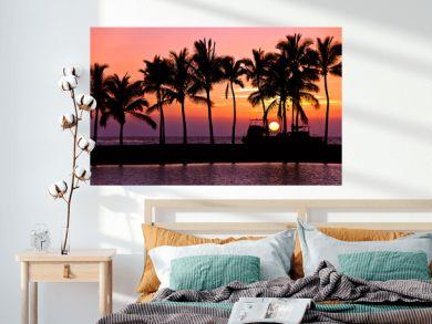 Setting sun with palm tree and boat silhouettes at Anaehoomalu Bay, Big Island, Hawaii