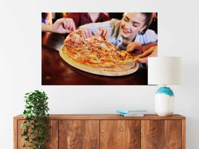 A group of friends eat pizza at a bar or pizzeria.
