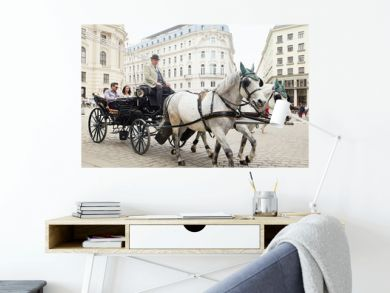 Vienna, Austria - 15 April 2018: a cab driver in a carriage with two horses drives tourists around the city.