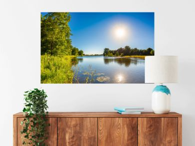 Summer landscape with trees, meadows, river and bright sun