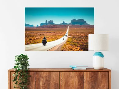 Biker on Monument Valley road at sunset, USA