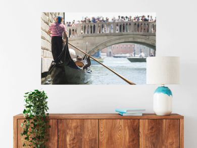 Venice, Italy - May 21, 2017: The gondola floats along the old narrow street in Venice. Gondola is the most attractive tourist transport in Venice.