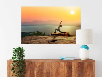 Woman practice yoga on mountain with sunset or sunrise background