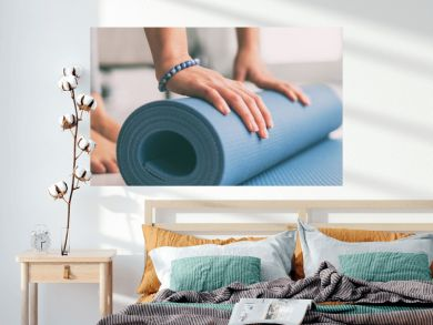 Yoga at home active lifestyle woman rolling exercise mat in living room for morning meditation yoga banner background.