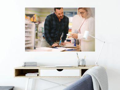 Pharmacist showing medicine to customer in pharmacy