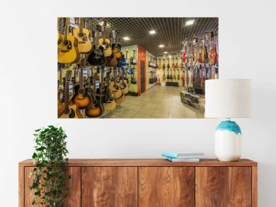 A row of different electric guitars hanging in a modern musical shop