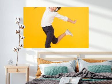 The best dancer. Adorable small dancer moving to music playing in headphones. Little dancer performing ballet leap on yellow background. Cute girl dancer dancing back to school dance