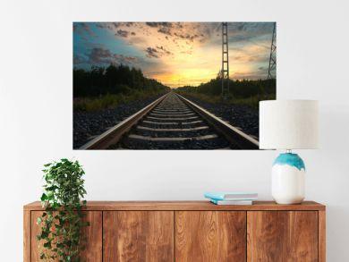 Long railroad track leading into a beautiful sunset.