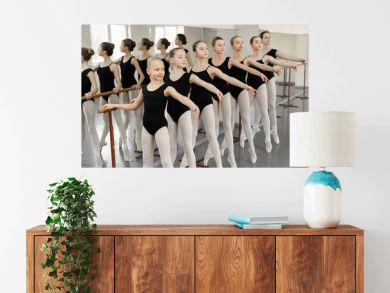 Ballet background, young ballerinas training. Female dancers legs in pointe shoes, making exercises. Classical dance school