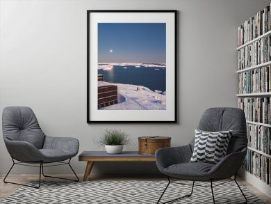 Antarctic research Vernadsky station buildings next to the Antarctica shoreline. Stunning winter landscape. The snow covered land surrounded by the frozen ocean. The harsh environment. Night scene
