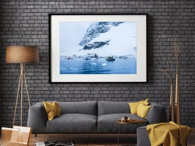 Snowfall over the motor boat with tourists and kayaks in the bay with rock and glacier in the background, near Almirante Brown, Antarctic peninsula