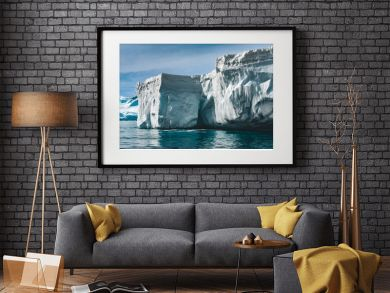 Close-up sunlit iceberg. Antarctica scene in blue and white tints. Amazing snow covered block of ice with icicles floating among the polar ocean. The cloudy sky background. Picturesque winter scenery.