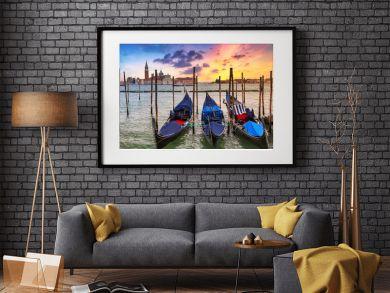 Venetian gondolas at the harbor and San Giorgio Maggiore island at sunset, Venice. Italy