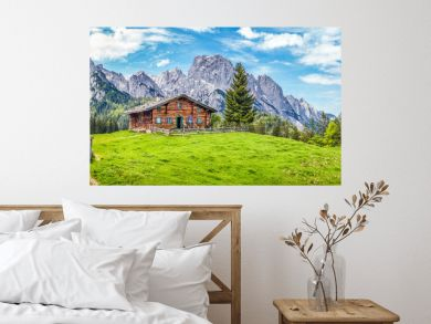 Idyllic landscape in the Alps with mountain chalet and green meadows