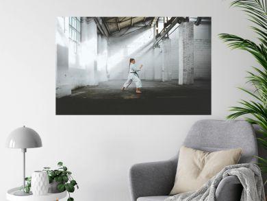 Caucasian female in Kimono practicing karate, Japanese martial arts. Old warehouse indoor shot