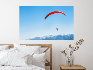 Sportsman on red paraglider soaring over the snowy mountain peaks