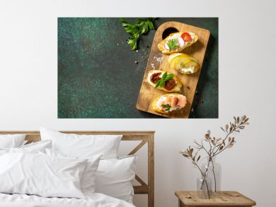 Italian Antipasti snacks set for Wine. Variety Brushetta with Soft Cheese, Pear, Radish, Salmon and Dried Tomatoes served on a rustic wooden board on a stone table. Top view. Copy space.
