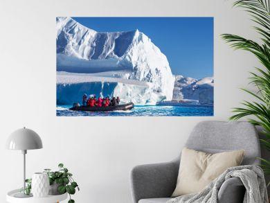 Tourists sitting on zodiac boat, exploring huge icebergs driftin