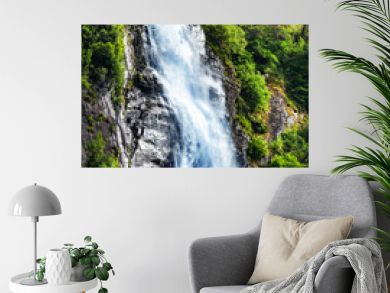 Panoramic beautiful deep forest waterfall in norway near blue ocean. Waterfalls mountain view close up.