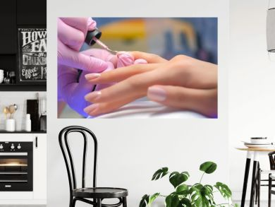 Manicurist master is covering painting client's nails shellac, hands closeup. Professional manicure in beauty salon. Hygiene and care for hands. Beauty industry concept.